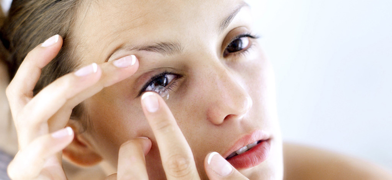 Woman putting her contacts into the eye
